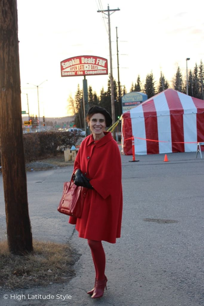 Alaskan woman in red cape, tights and boots with black gloves, beret