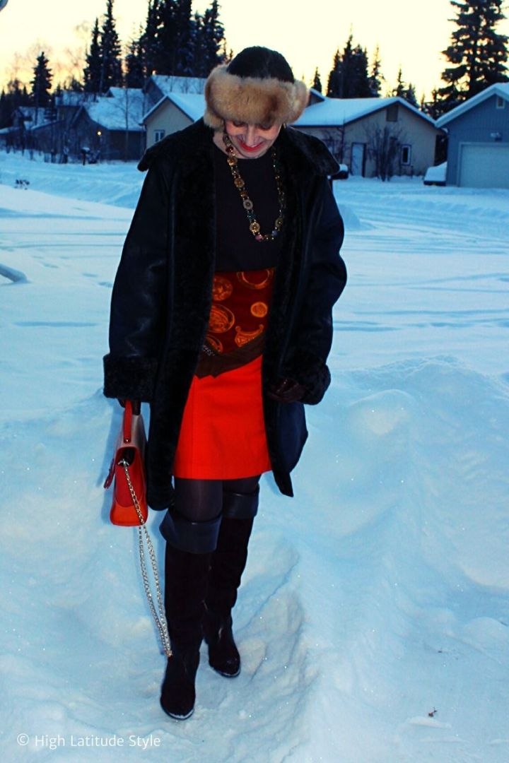 Alaskan fashion blogger in tall boots, shearling coat, headband and orange skirt