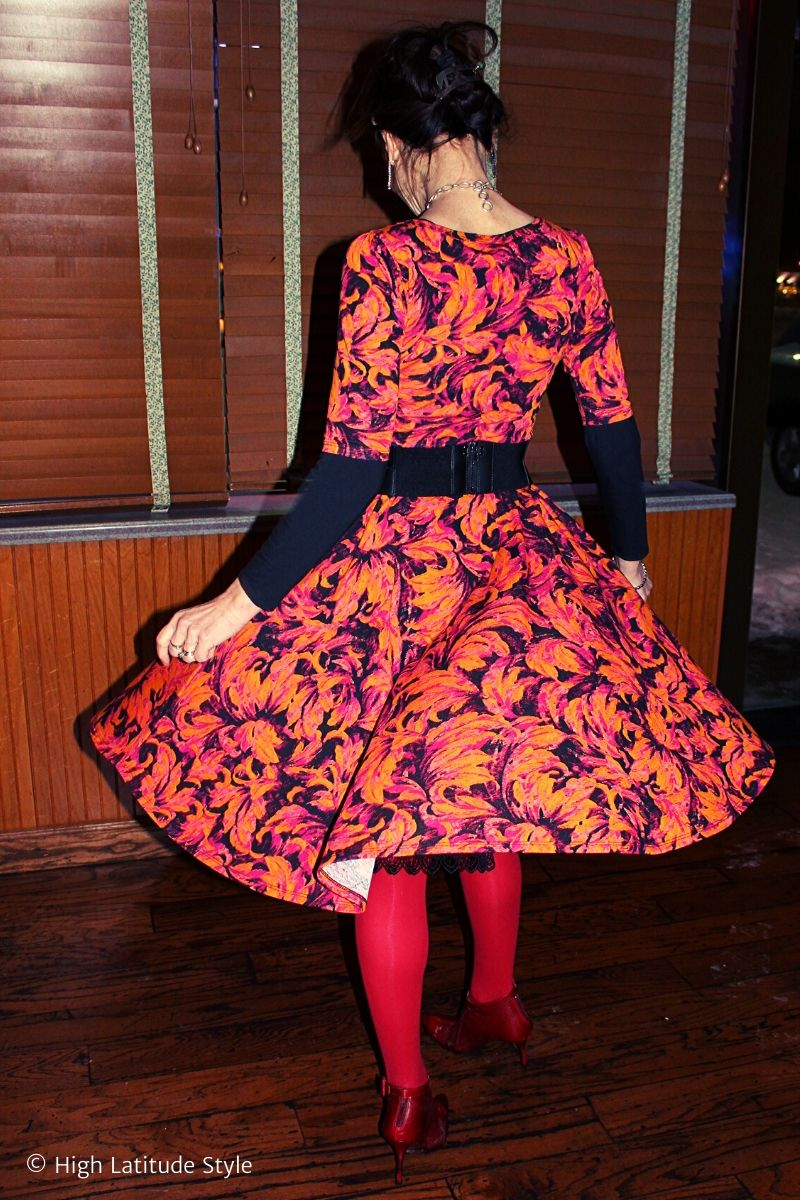 Nicole twirling in an orange burgundy black fit-and-flare dress