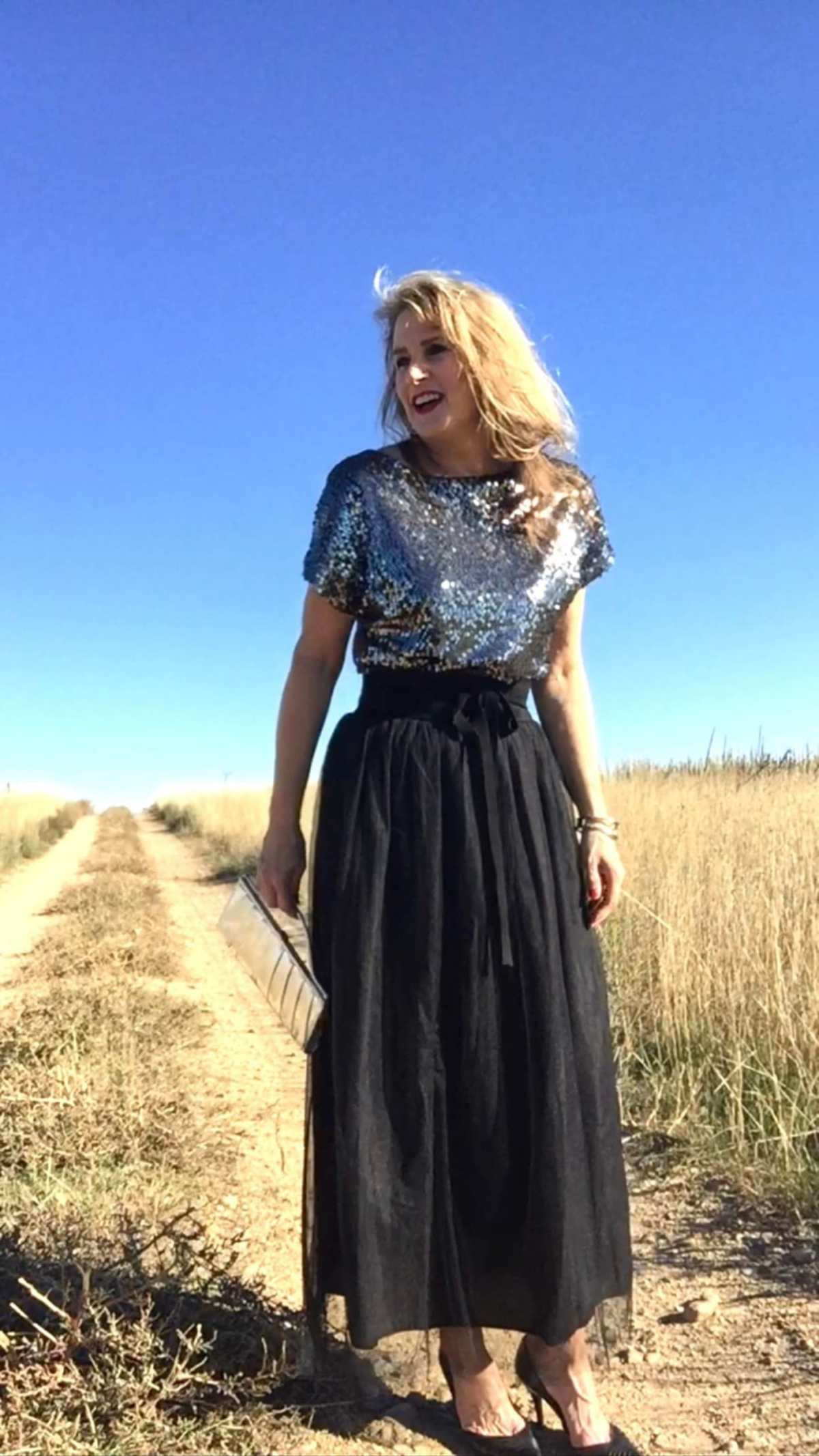 Cynthia Scurry of Middle Sister Style in silver sequin top, tulle maxi skirt, black pumps with clutch
