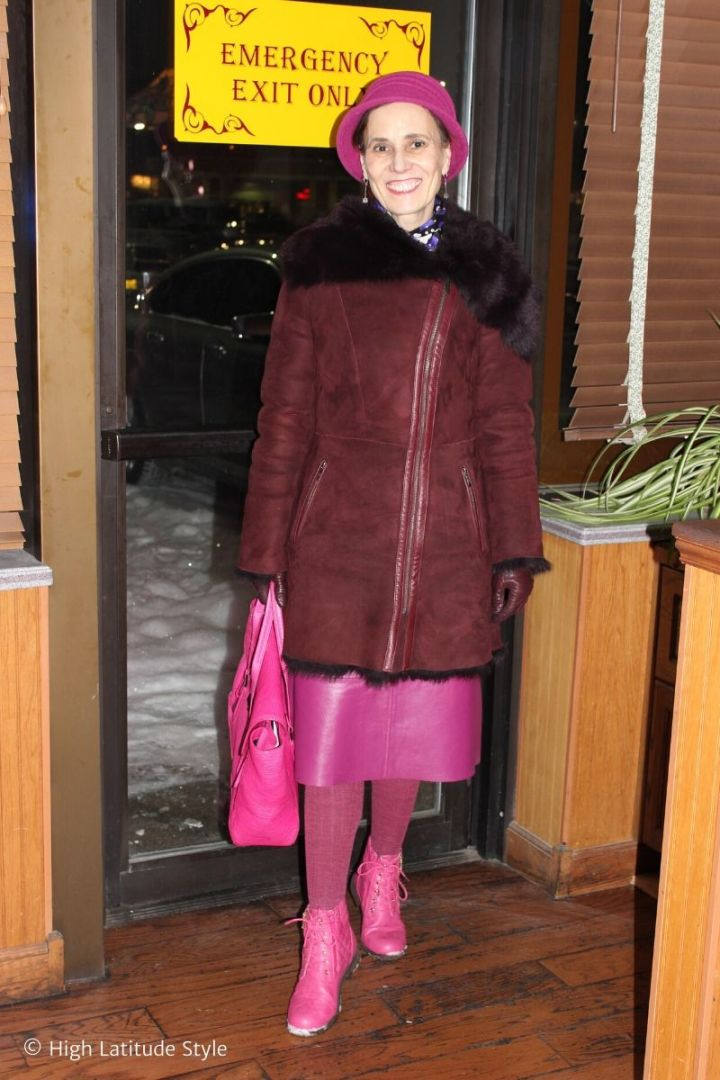 stylist in burgundy shearling coat and gloves, pink hat, skirt, bag and tights