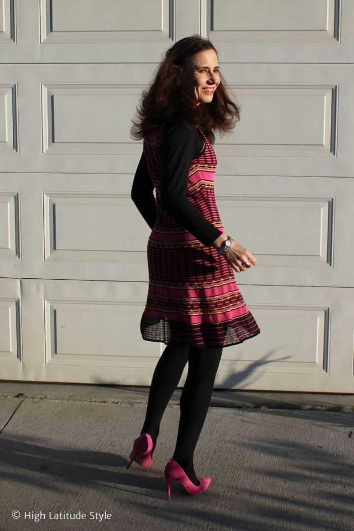 mature woman twirling in pink striped fit-and-flare dress