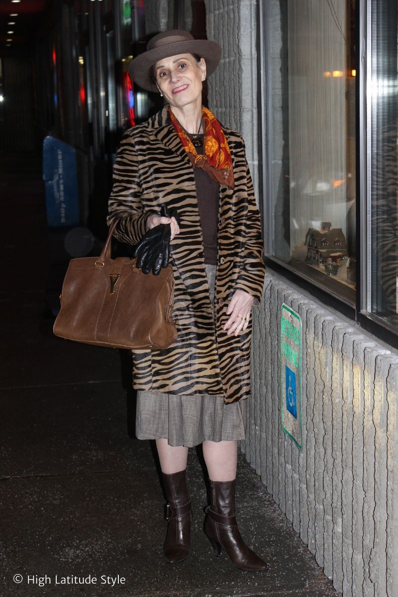 over 50 years old fashion blogger in zebra coat, glencheck pleated skirt, brown sweater, silk scarf and hat