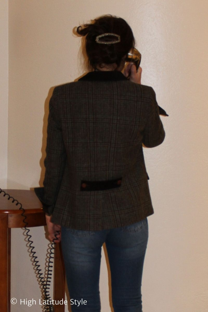 back view of stylist on the phone in plaid blazer and jeans with barrette updo