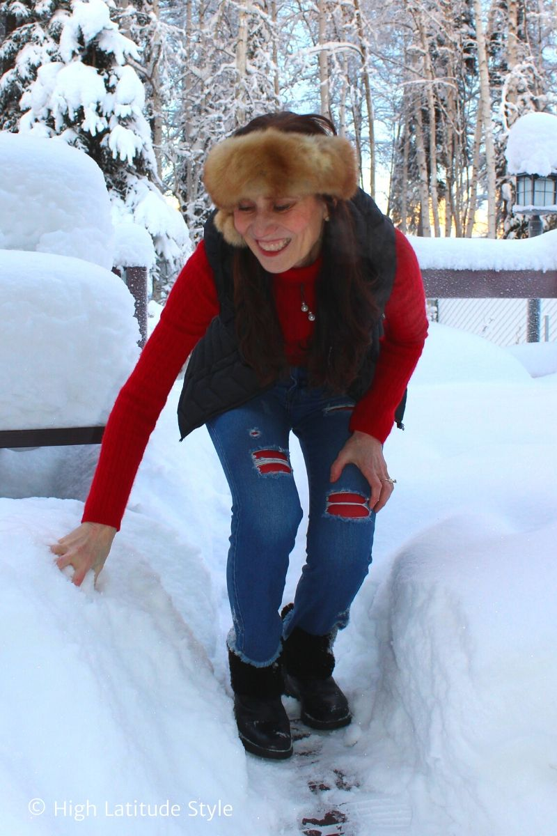 blogger in vest, denim pants, tight, sweater, head band, boots picking up snow