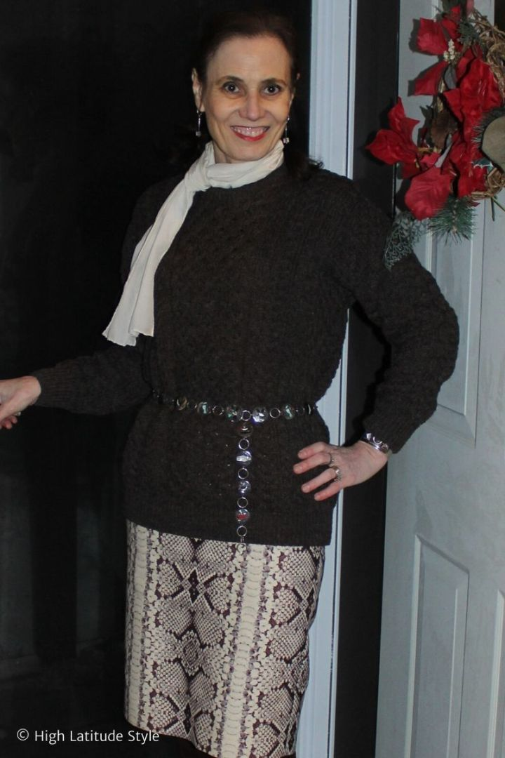 stylist in winter outfit with wool skirt, knit sweater, silk scarf, ethnic belt