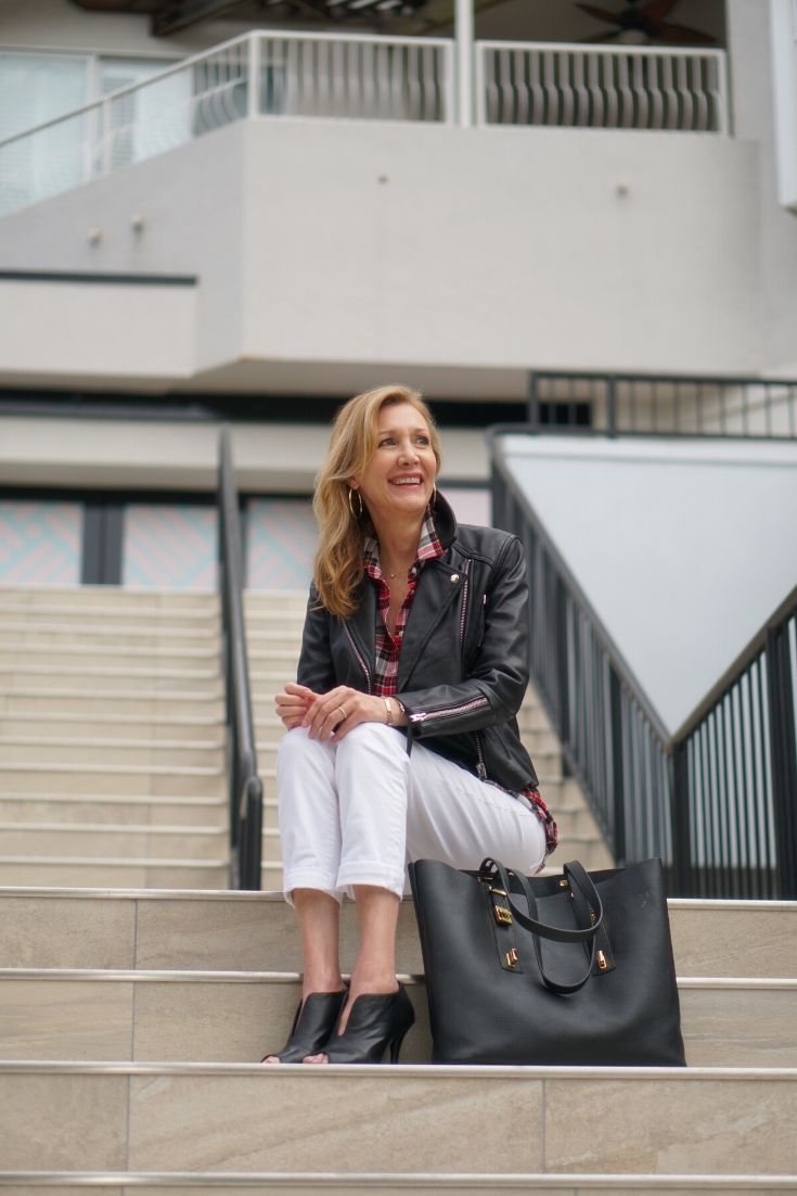 Nina Bandoni of Sharing a Journey in white pants, leather jacket and open toe-booties