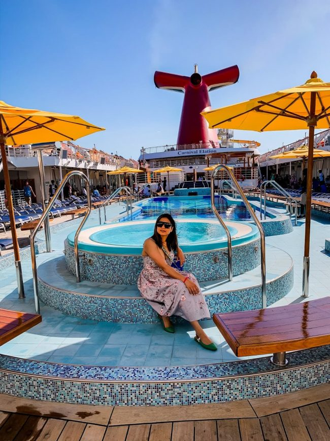 Top of the World OOTD Readers' Fav Saumya of Myriad Musings sitting at a pool on a cruise ship