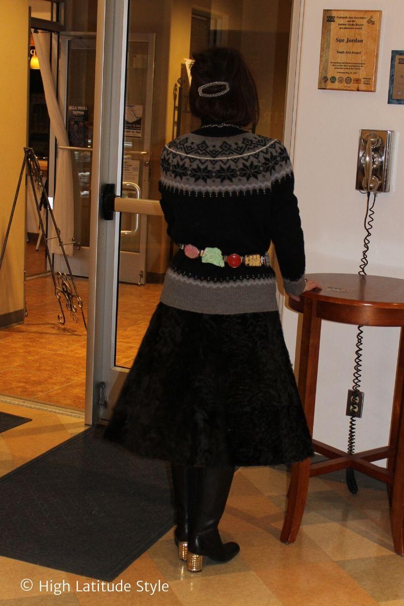over 50 years old Alaskan in A-line fur skirt, turtleneck sweater, gemstone belt, barrette