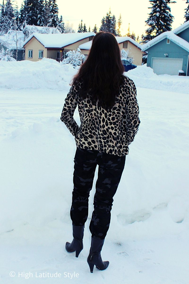 Alaskan woman posing in camouflage joogers and leopard pring jacket in a snow covered neighborhood