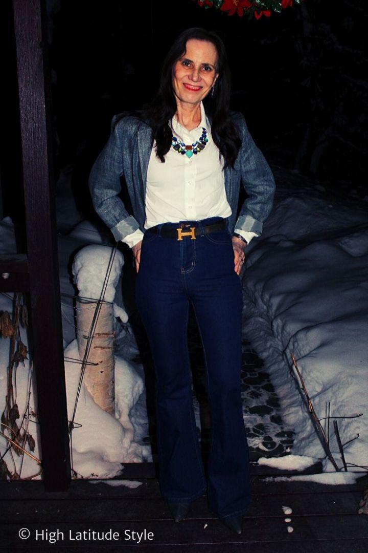 stylist in flare dark high waist jeans, denim booties, white blouse, petrol blazer