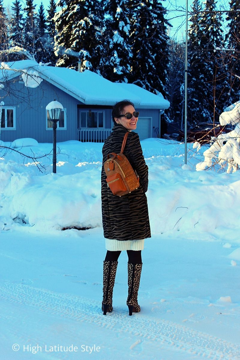 midlife blogger in leopard print boots, zebra coat, white dress,sunnies carrying a backpack in a snowed-in neighborhood