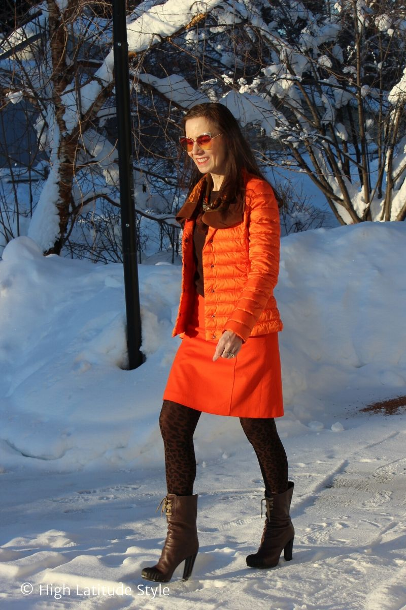 midlife woman in orange suit, leopard print tights, heeled ducks walking on snow