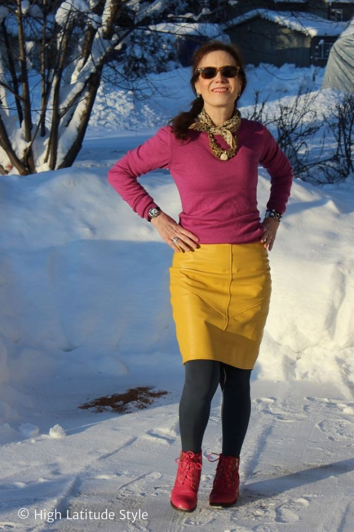 older woman in yellow leather skirt, matching scarf, pink top, teal tights