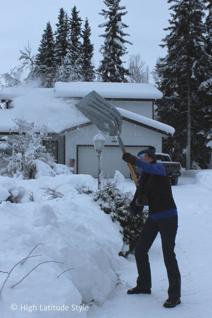 lifestyle blogger removing snow from the driveway in sunglasses, vest, jeans, boots, scarf, vest, sweater, cableknit hat