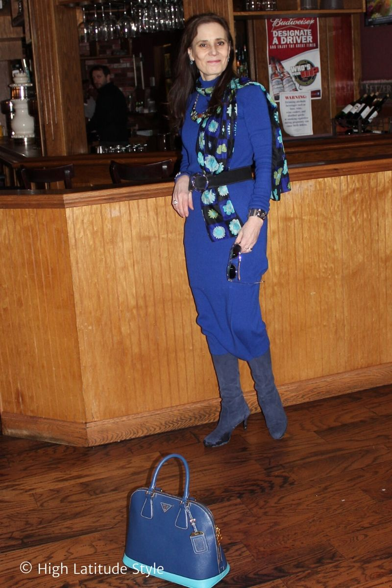 stylist wearing a blue dress, boots, belt, statement necklace and floral scarf holding MessyWeekend sunglasses