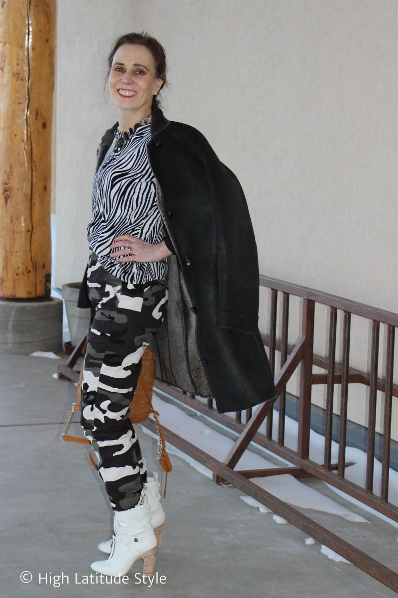 fashion blogger in snow camouflage pants, zebra top, shealing, white heels carrying a backpack