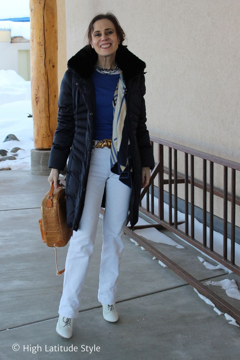 fashion blogger in casual posh winter style with pants, down jacket, layered tops, scarf, necklace, belt