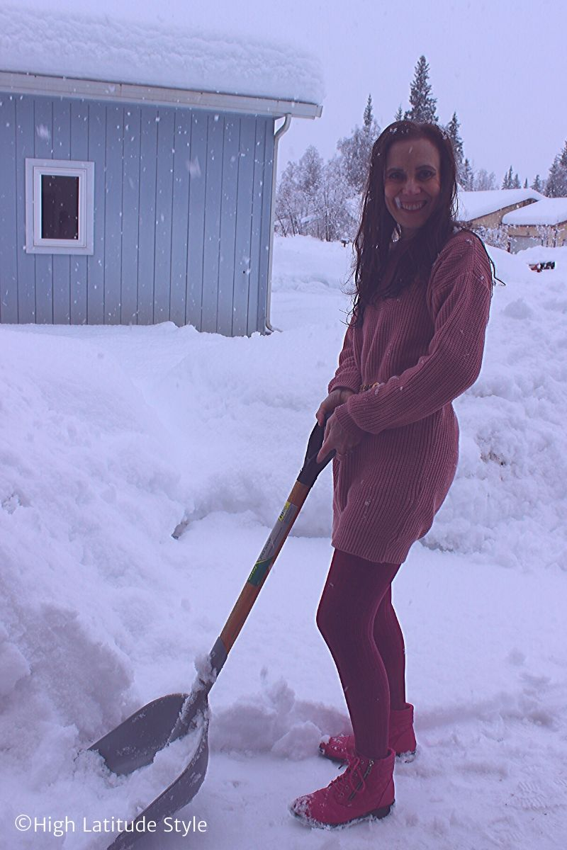 Alaskan blogger using snow shoveling as excercise in sweater, tights, booties
