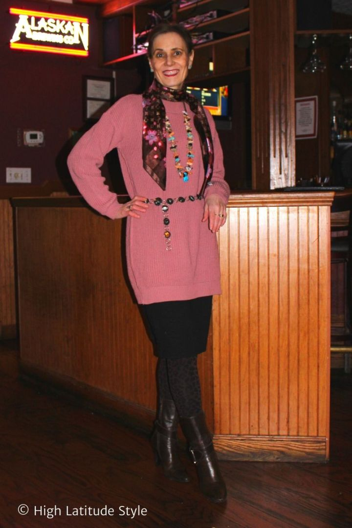 style blogger in pink sweater dress over knit skirt, leopard pattern tights with booties, scarf, necklace and belt