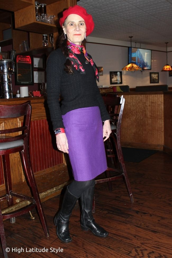Alaskan fashion blogger in red beret, black sweater, purple skirt, tall boots and tights