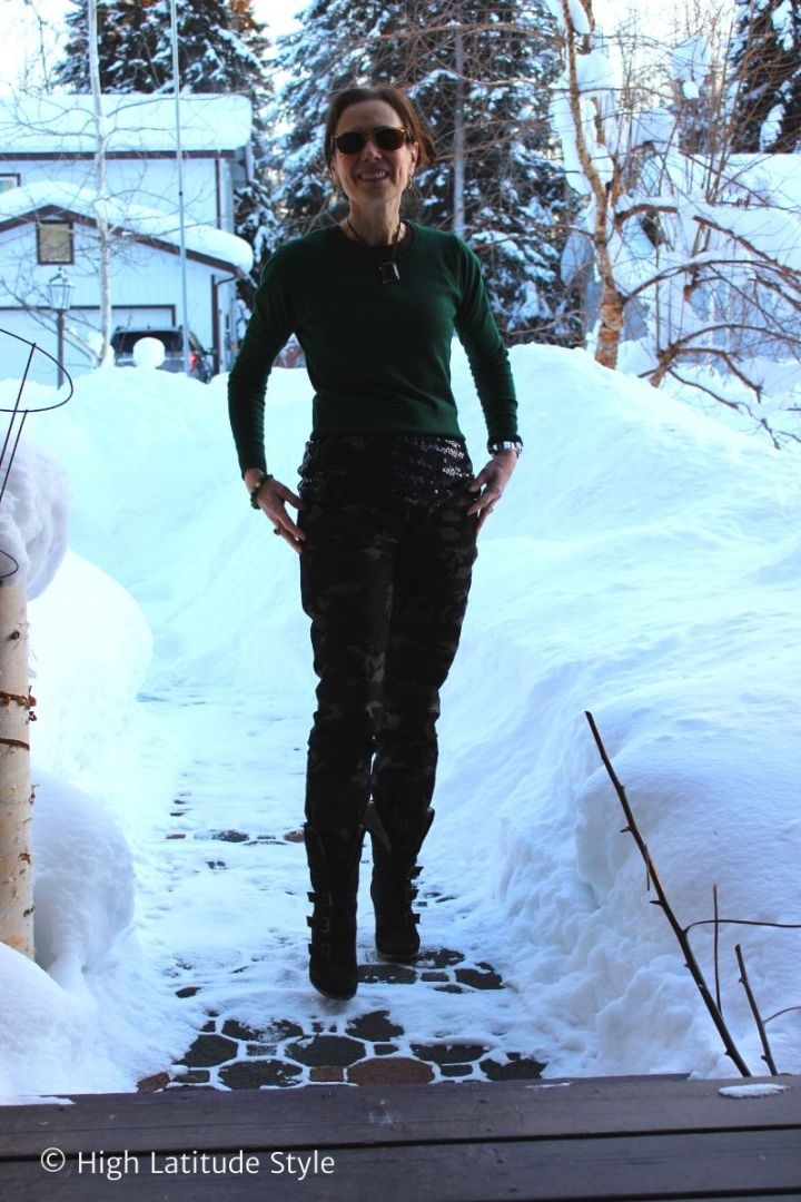 Alaskan blogger in sequin top under sweater, camouflage pants standing in high snow