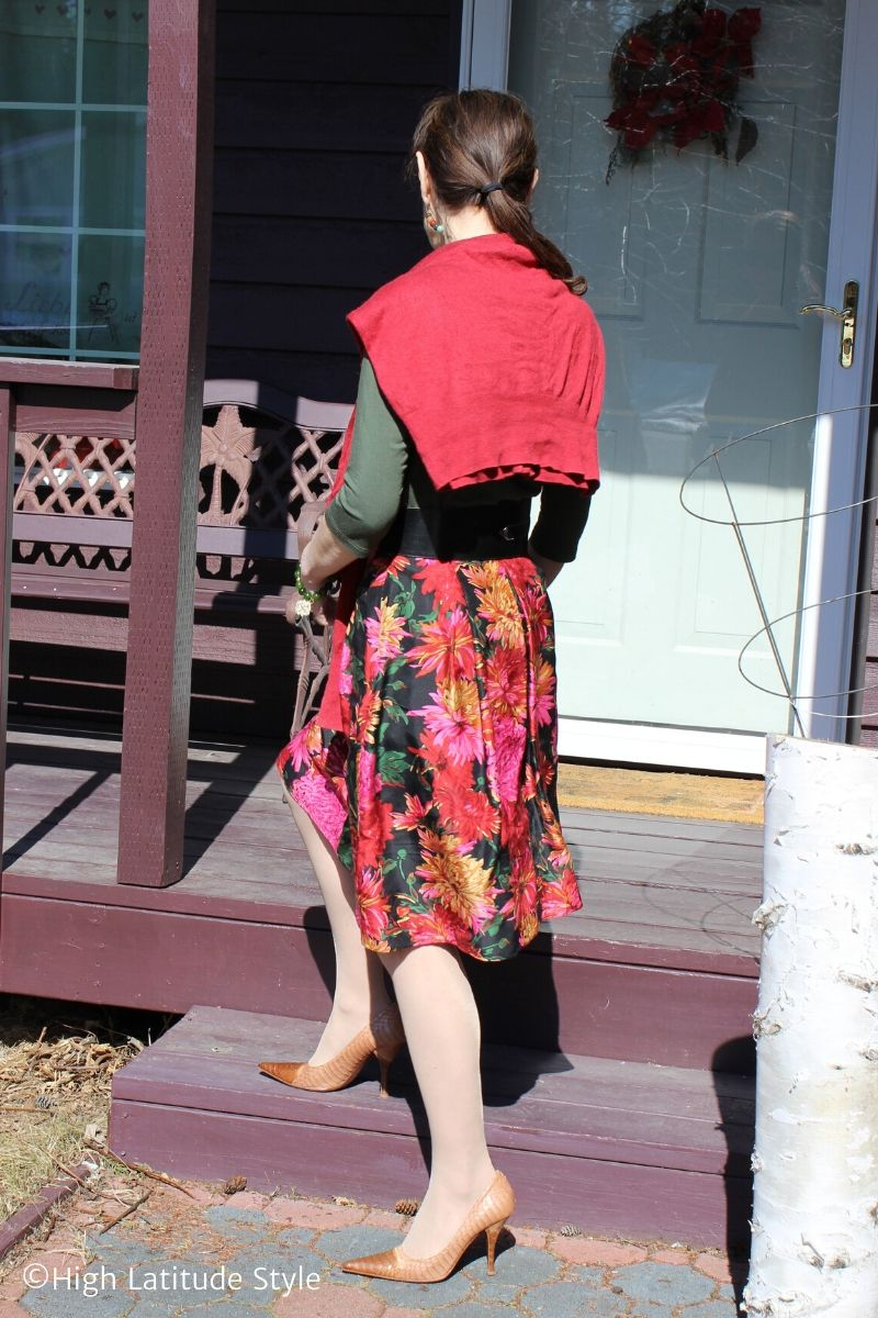 stylist walking up stairs in abstract floral skirt, green T-shirt, rost cardigan, bi-color pointy toe pumps