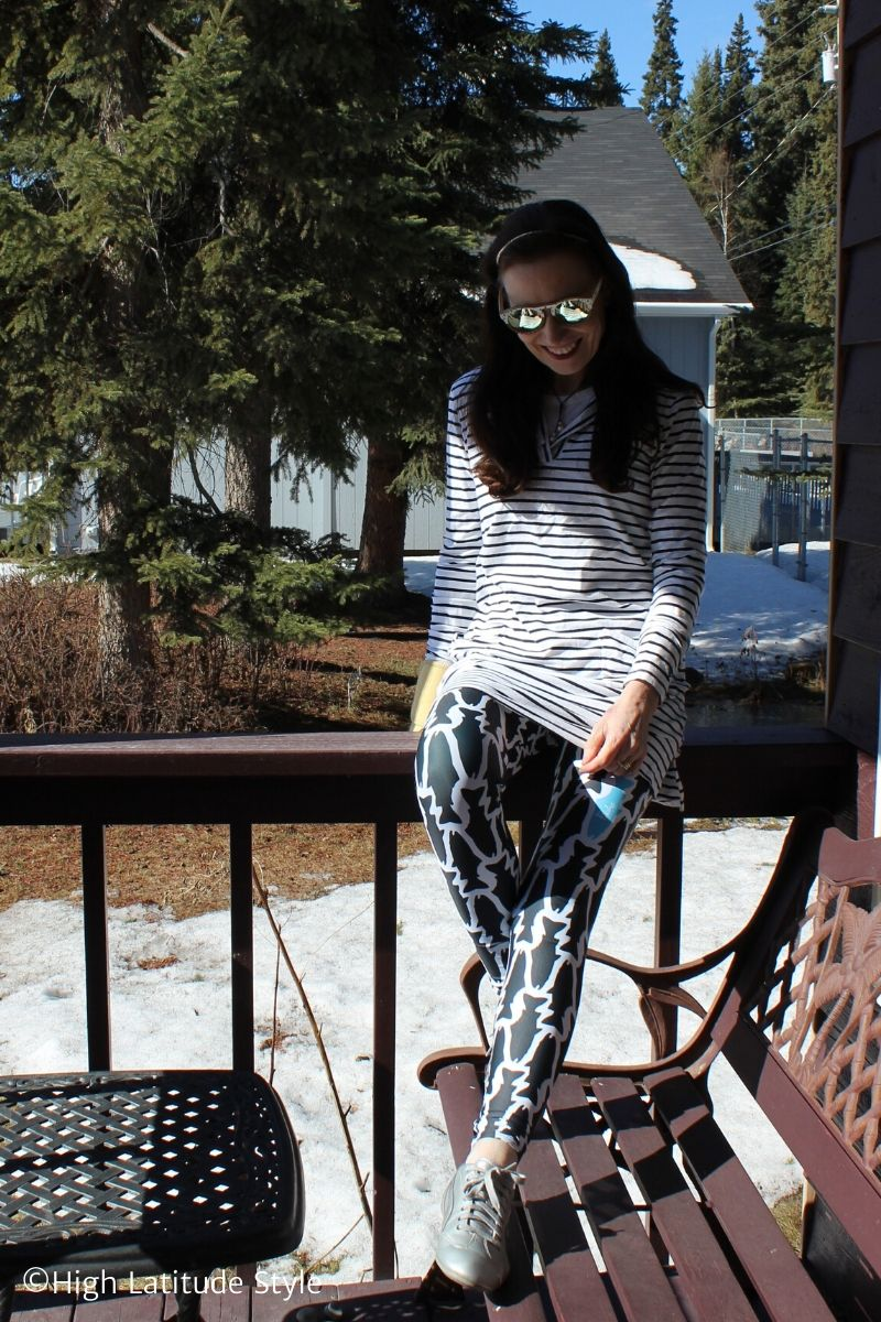 fashion blogger in athleisure outfit of fish print leggings, stripped hoodie top, mirrored sunnies and puma shoes