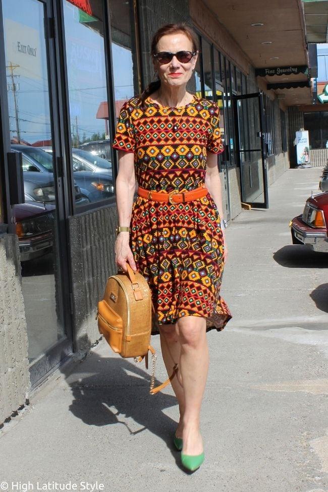 trendsetter in ikat striped print A-Line dress green shoes, tan backpack, sunglasses, xo belt