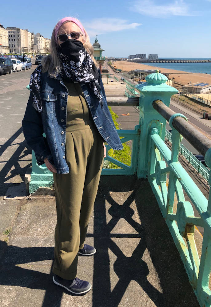 Top of the World Style Winner Penny Kocher in olive jumpsuit, sneakers, denim jacket, head scarf and scarf mask