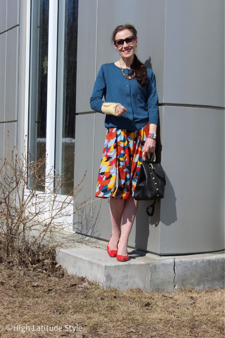 stylist in teal top and multi-color print skirt with red pumps