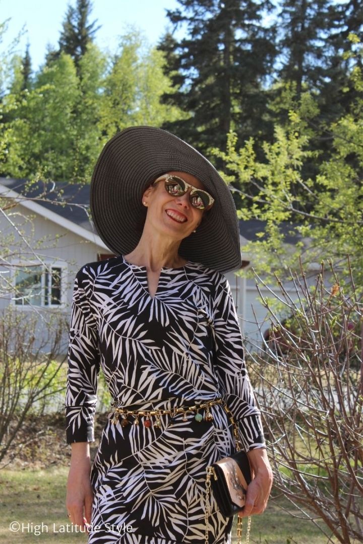 50 years old woman in leaf print dress, sunglasses, hat with belt and mini bag