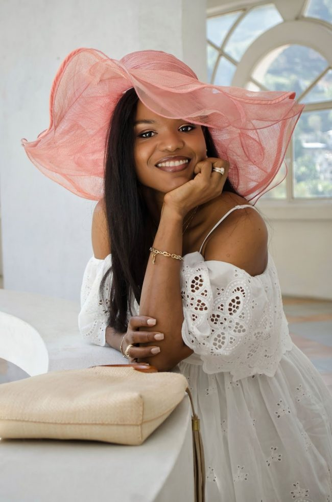 Iris of La Moumous in pink hat and white eyelet lace dress