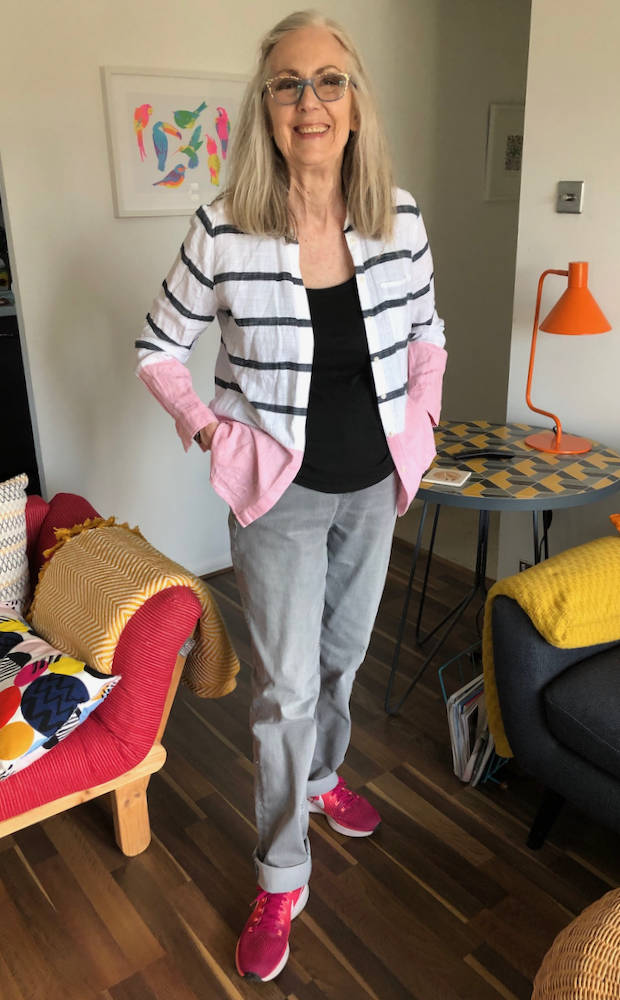 Penny in striped cardigan, black top, pink sneakers, gray pants