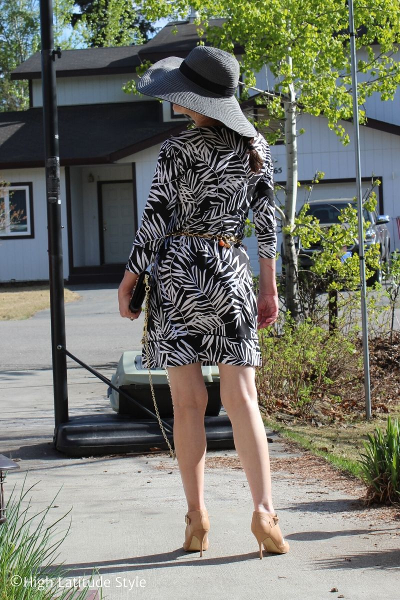 stylist in busy print vacation dress flesh color heels and black hat