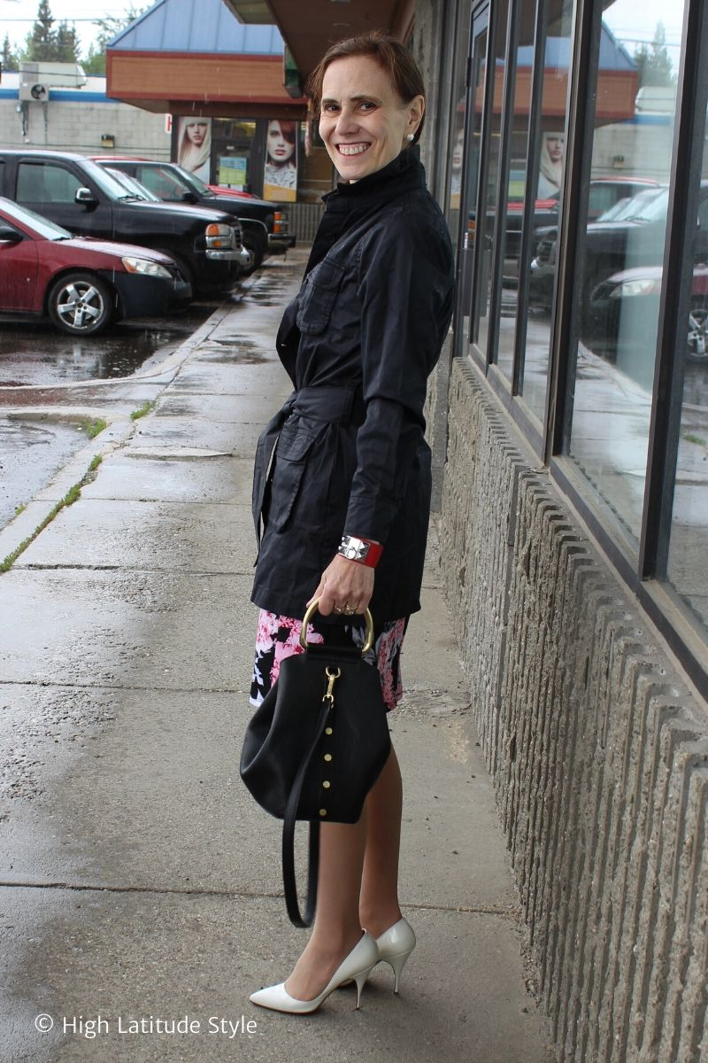 over 50 years old woman in trench coat, dress, pumps and pearl ear studs