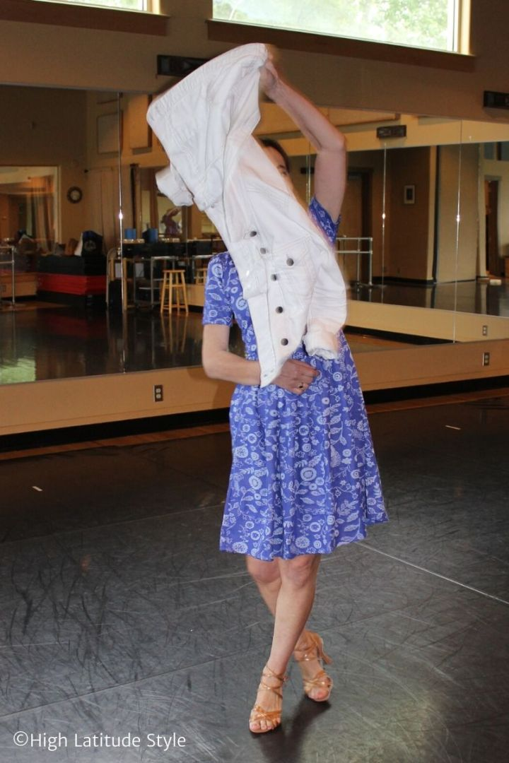 performing a dance using a jacket in a girly floral dress