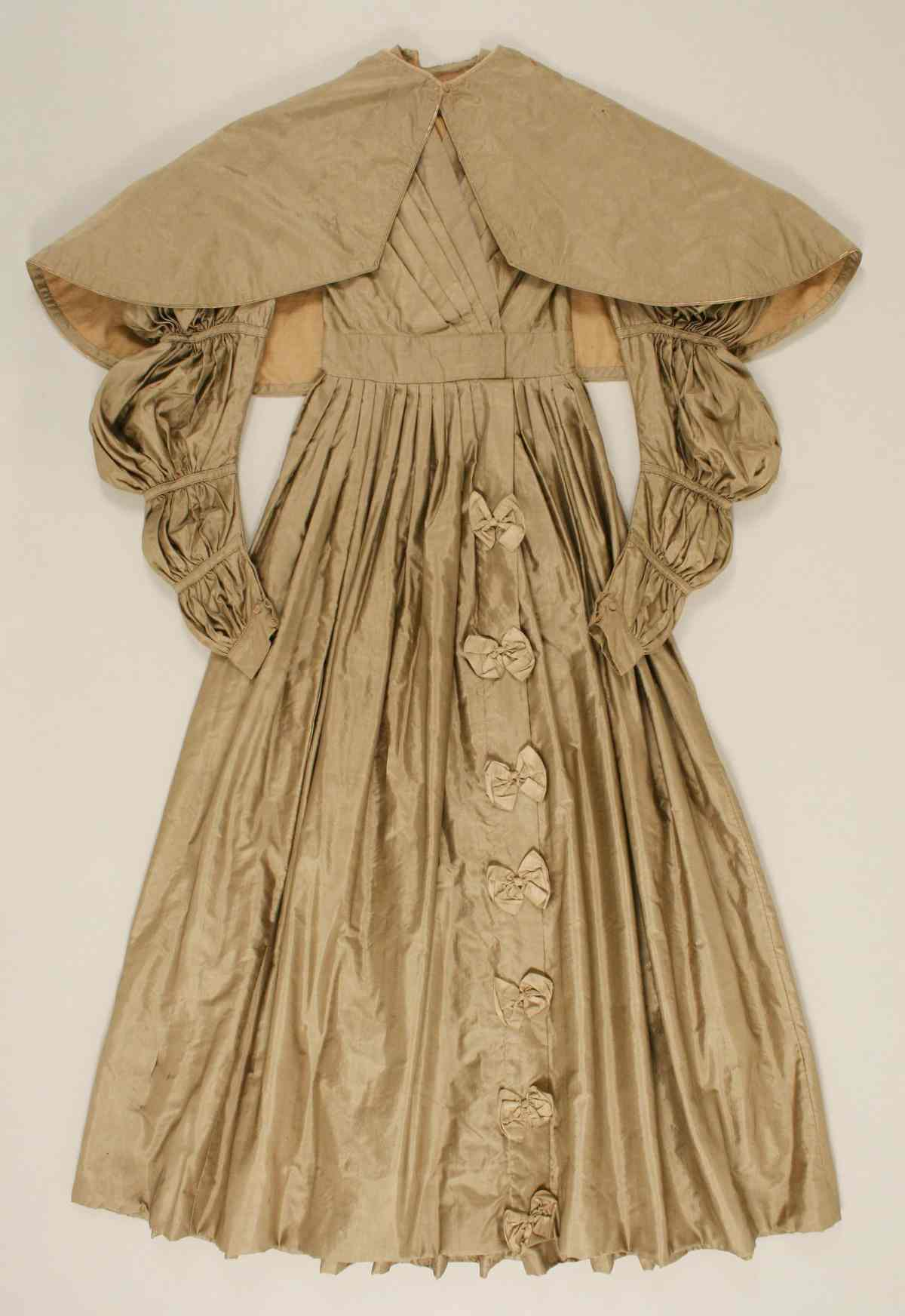 American dress with puff sleeves, pelerine, wide skirt and bows