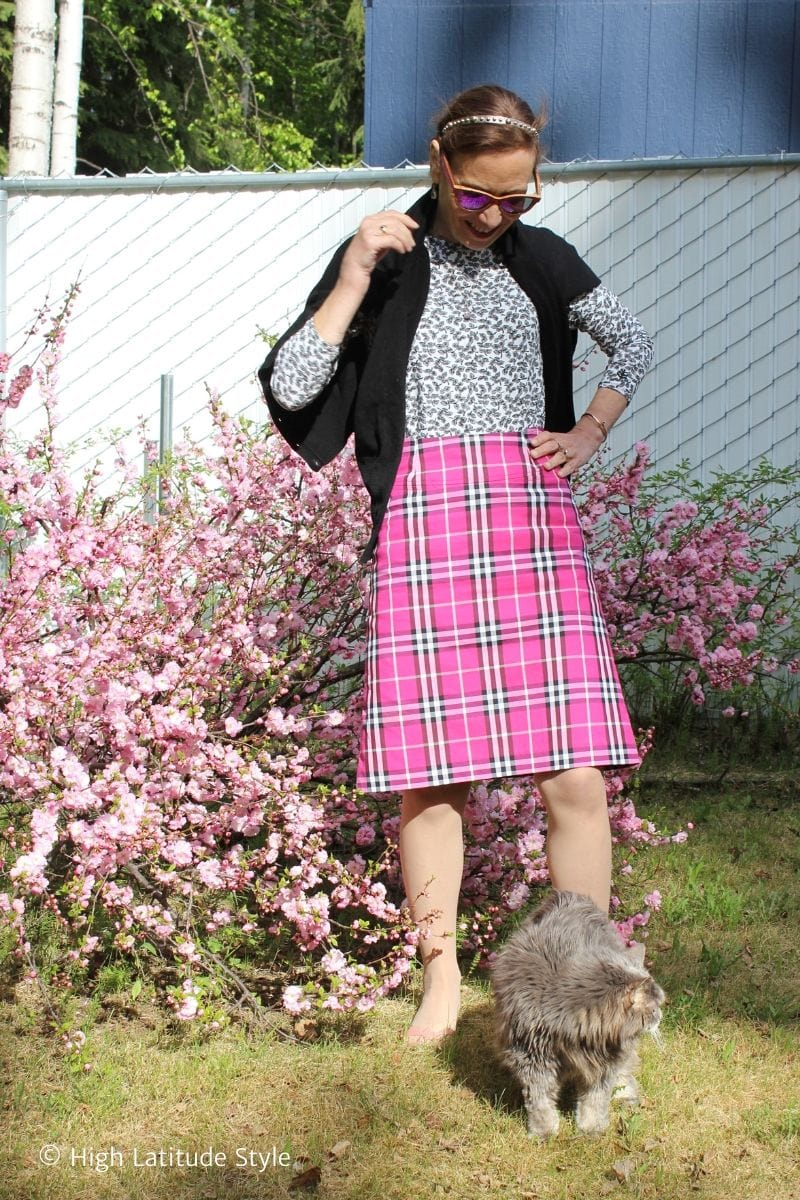 style blogger styling a pink plaid skirt for work with a leave print top, pantyhose