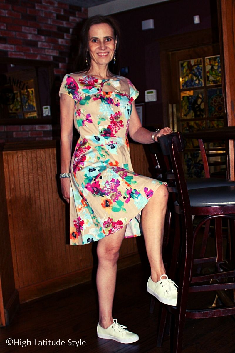 fashion blogger in flower print dress with white sneakers, jewelry