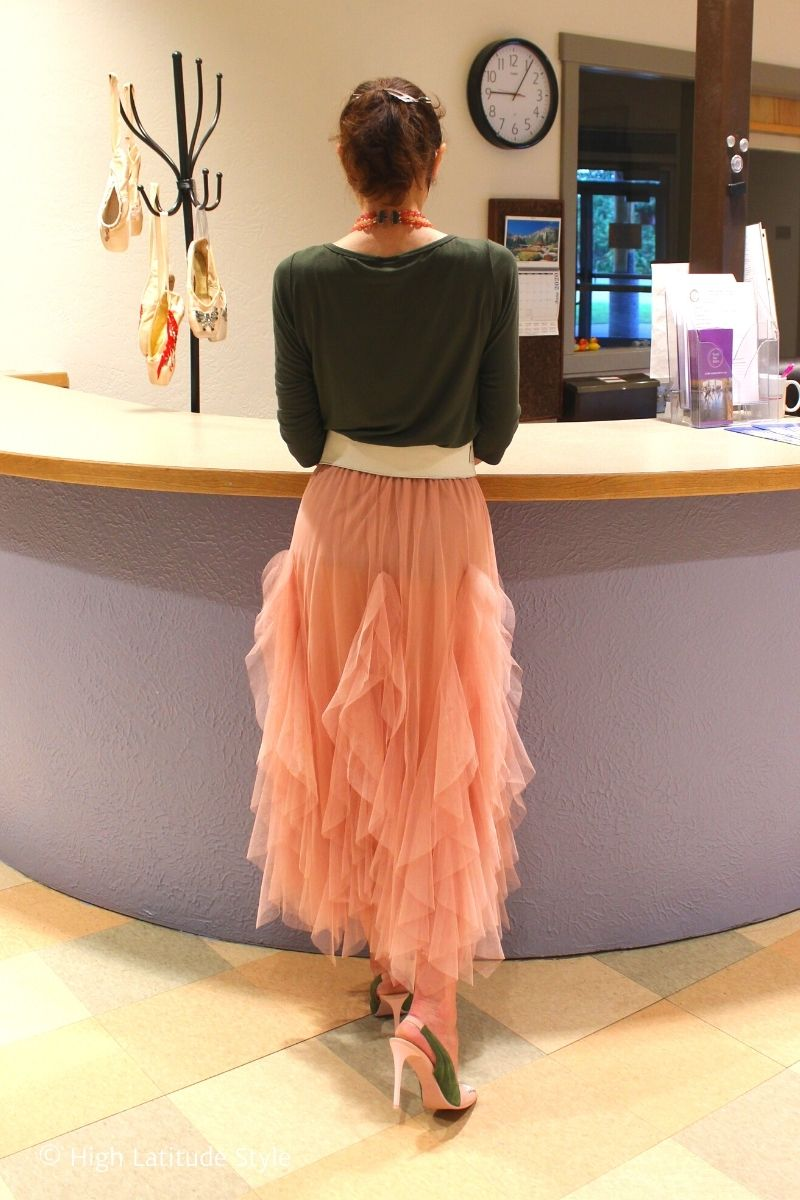 blogger in tulle skirt over 50, T-shirt, belt, heels, barrette in front of a counter