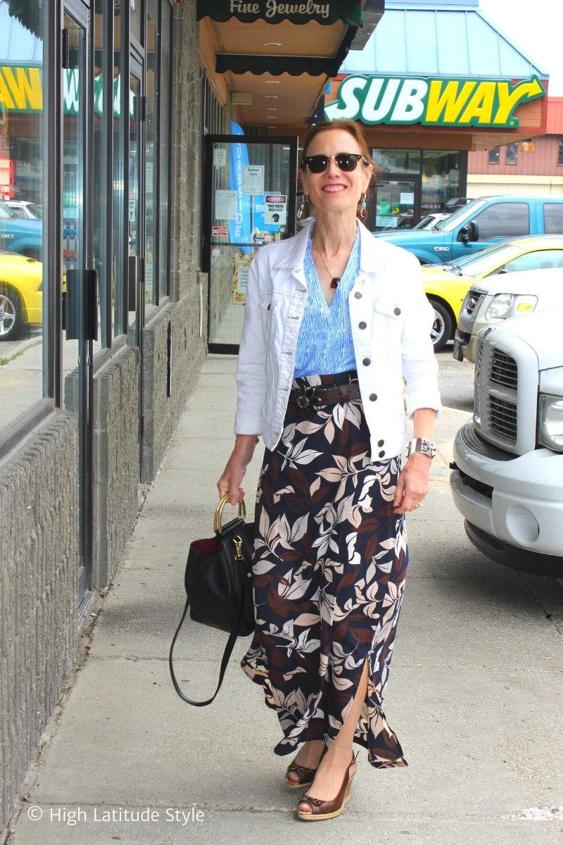 style book author in UV secure white jacket, multi color skirt, blue and white top walking in a mall outside