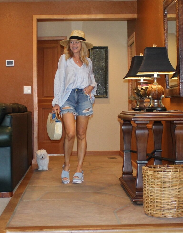 Cheryl of Northwest Mountain Living in distressed shorts, peasant blouse, hat, plateau sandals with straw bag