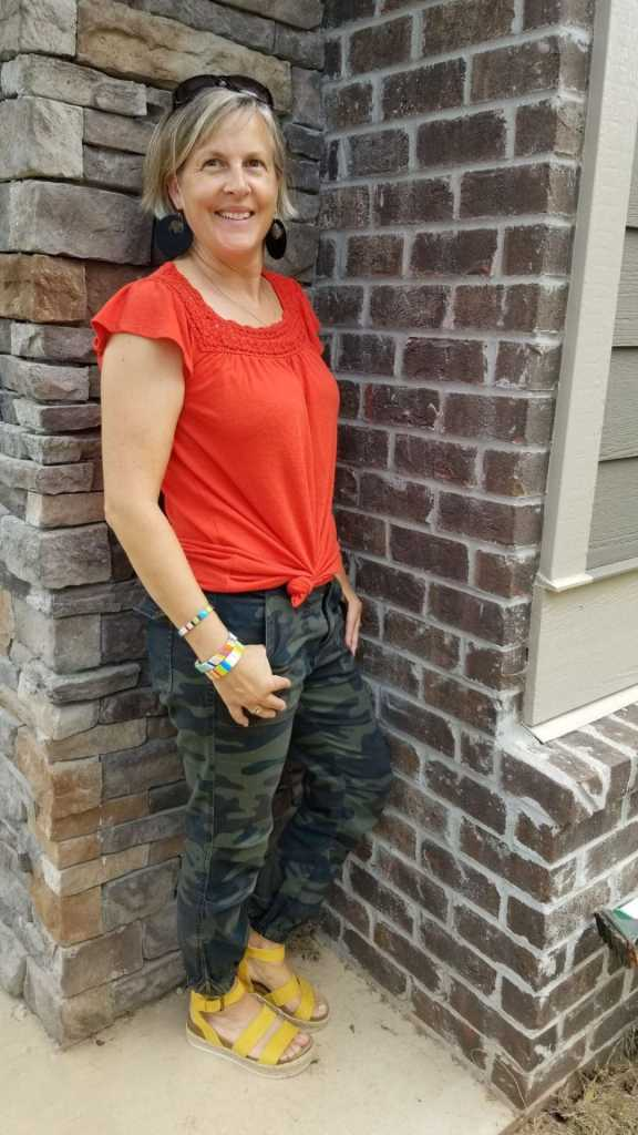 travel blogger Mireille in orange top, yellow sandals and camouflage pants