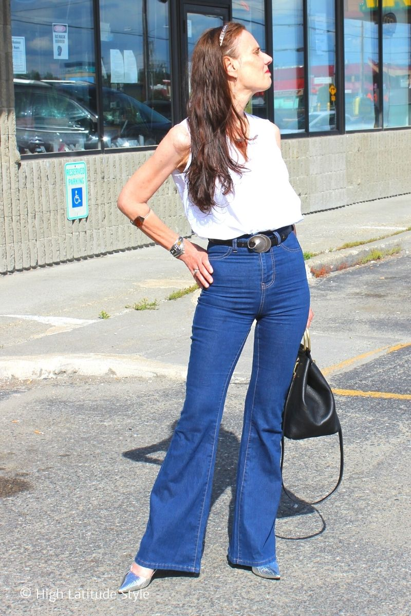 Nicole in high-raise denim pants, white top with bag, headband and arm candies