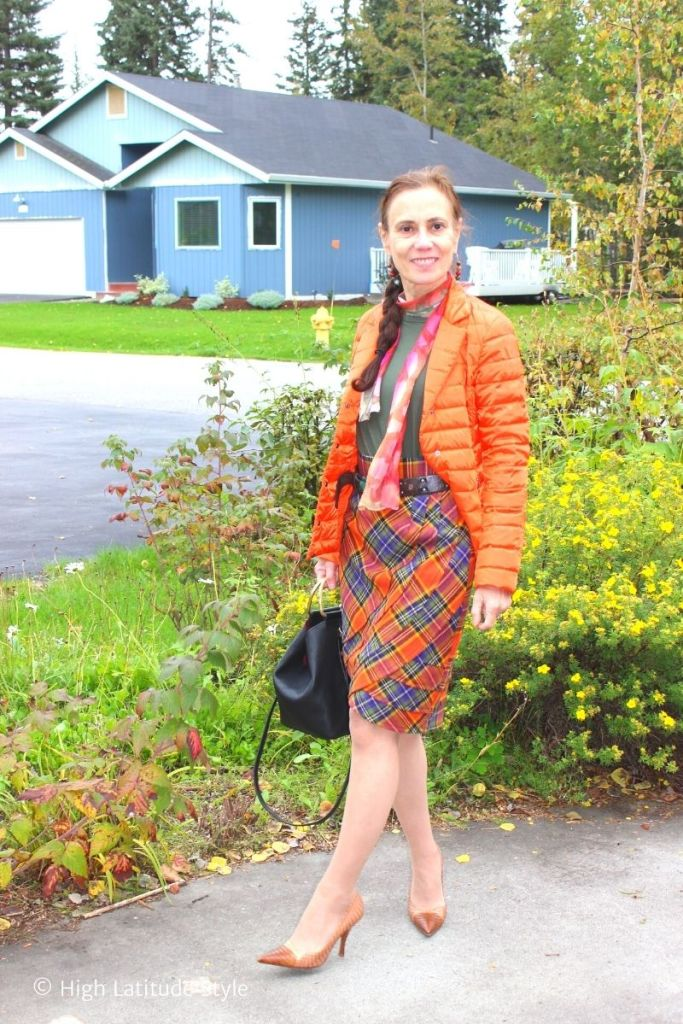 over 50 years old style blogger in plaid skirt, scarf, puffer jacket, pumps