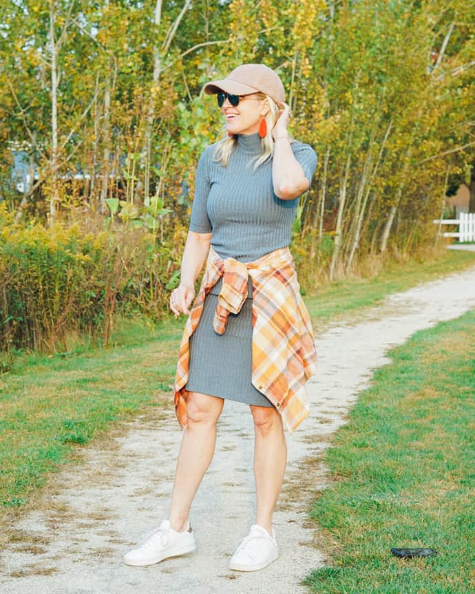 Jill in gray knit dress, sneaker, baseball cap, plaid shirt and long earrings