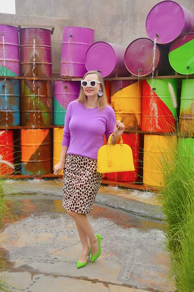 Katie in purple sweater, leopard print skirt, yellow bag and chartreuse pumps