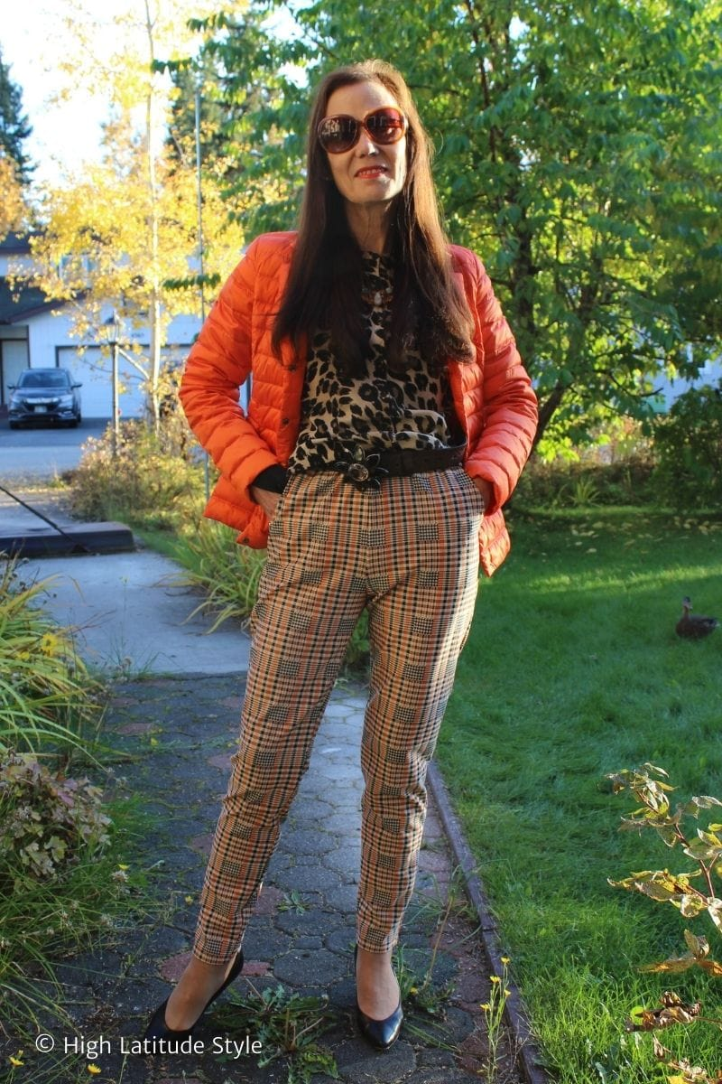 fashion influencer in plaid trousers, puffer jacket, leopard print cardigan, black pumps