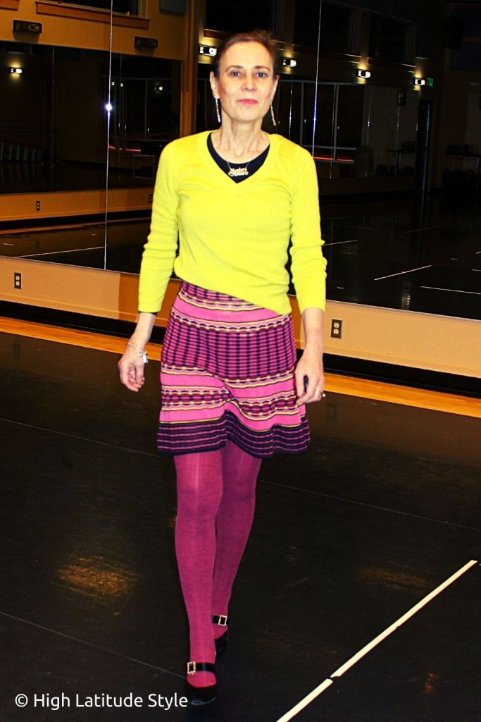 stylist in pink tights, skirt, yellow top and oNecklace customized jewelry